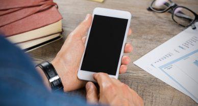 foto de homem mexendo no iphone com a tele preta
